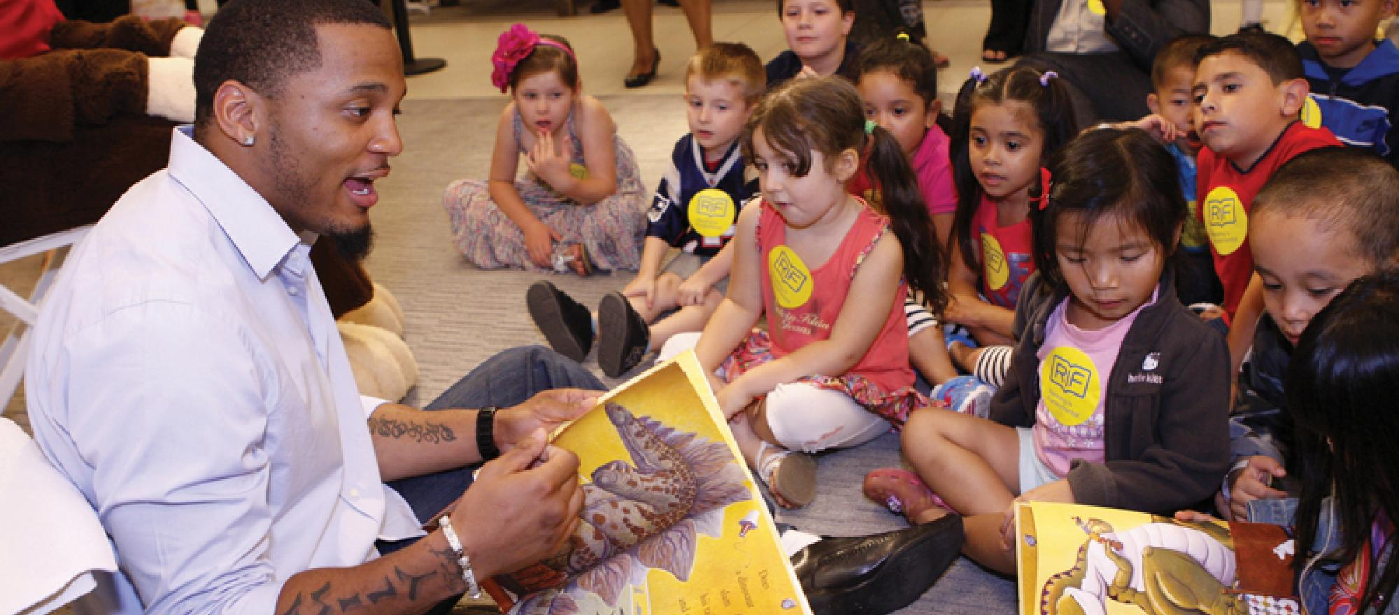 Patrick Chung, player for the New England Patriots, reads to children in Boston at the Macy's store. Macy's is a long-time sponsor of RIF.