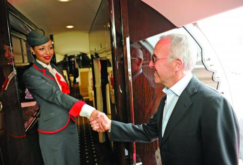A flight attendant welcomes VistaJet client Frank McCourt, chairman and CEO of McCourt Global, aboard a Bombardier Global 6000 (Photo: Mark Wagner)