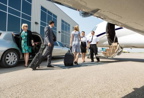 Customers exiting a limousine and immediately boarding their private business jet.