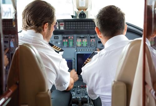 Pilot and copilot in a business jet cabin.