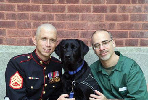 A wounded war vet and an inmate with a dog from Puppies Behind Bars.
